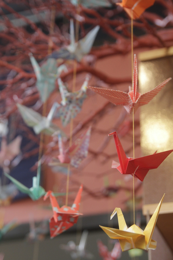 Origami mobile hanging from a red-painted branch